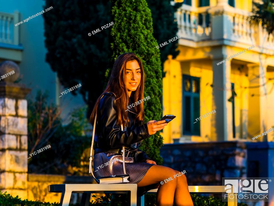 Stock Photo: Teen girl in park with smartphone in hand is smiling at camera.