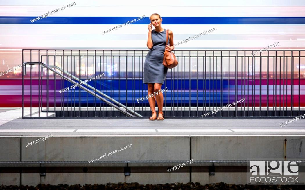 Stock Photo: Pretty, young female commuter waiting for her daily train in a modern trainstation, using her cellphone while waiting (color toned image).