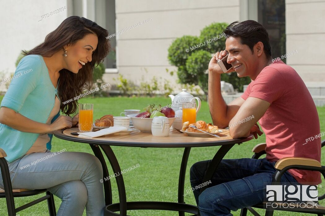 Stock Photo: India, Man and woman at breakfast table in garden.