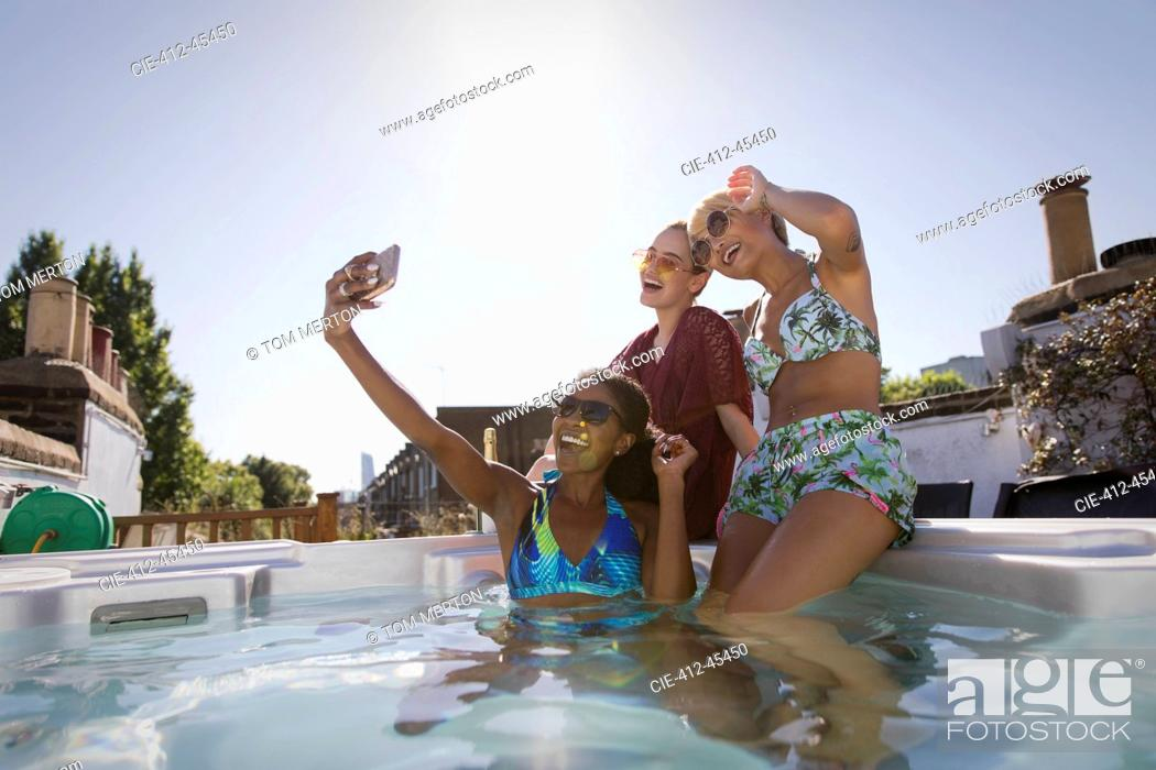 Photo de stock: Happy, carefree young women friends in bikinis taking selfie with camera phone in sunny, rooftop hot tub.