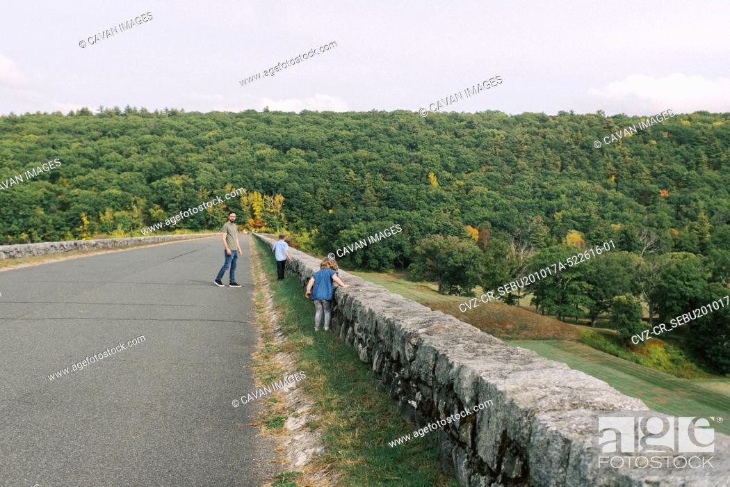 Stock Photo: A millennial father and his two children on a hike on top of a dike.