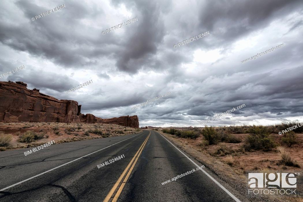 Stock Photo: Street in desert under clouds.