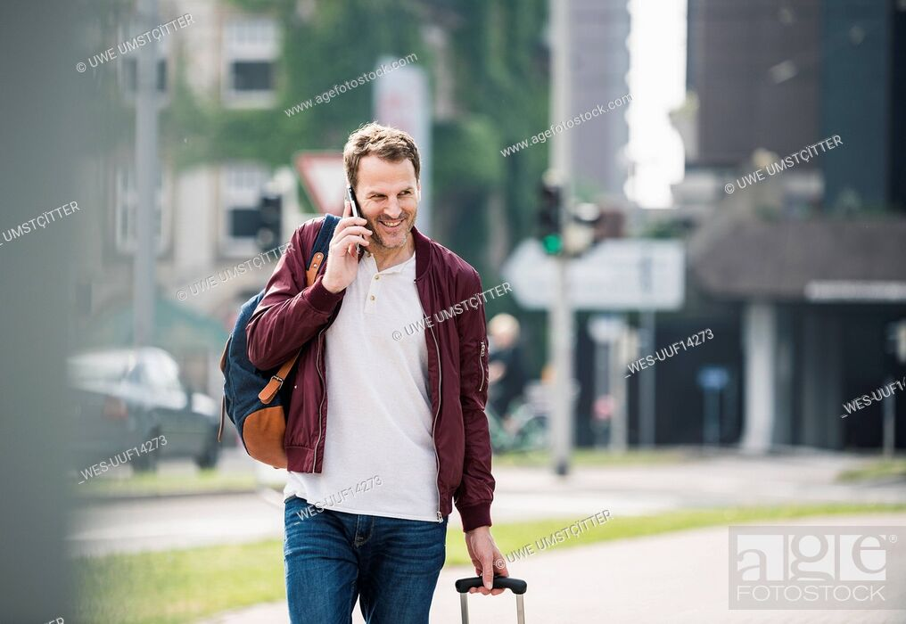 Stock Photo: Smiling man with rolling suitcase on cell phone in the city.