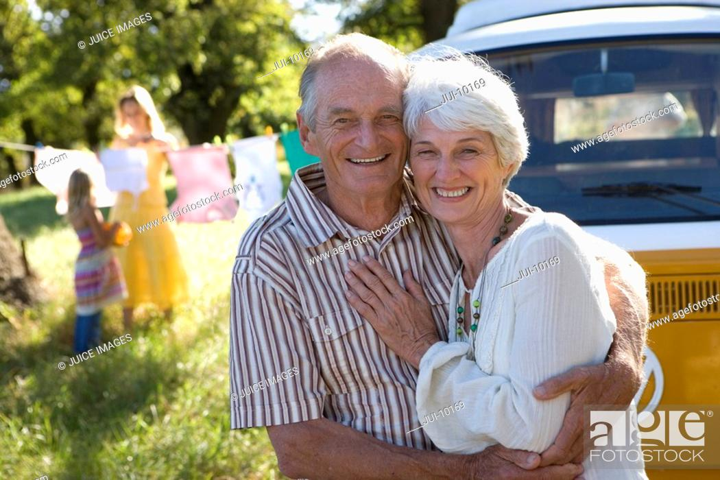 Stock Photo: Senior couple embracing by camper van, smiling, portrait.