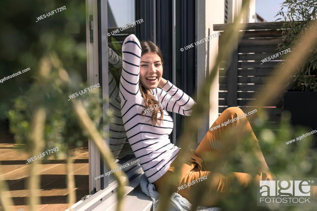 Stock Photo: Portrait of laughing young woman sitting on terrace at home.