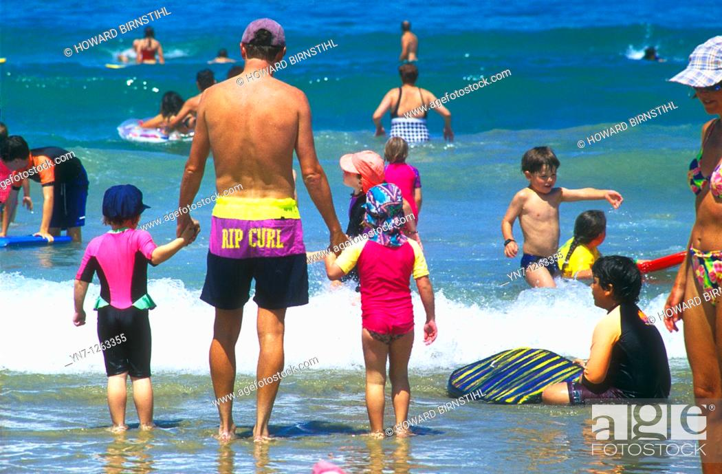 Stock Photo: Father and children at the beach watching the waves.