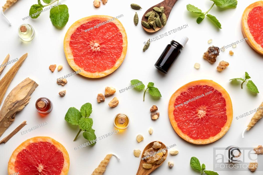 Stock Photo: Bottles of essential oil with fresh grapefruit, peppermint, white sandalwood, cardamon and other ingredients.