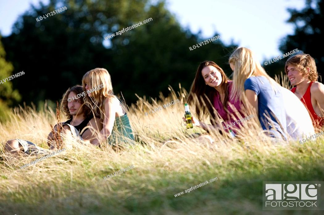 Stock Photo: A group of young people sitting in a park, drinking beers.