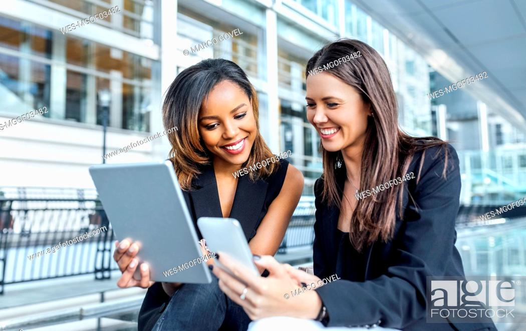 Stock Photo: Two businesswomen working with smartphone and tablet in the city.