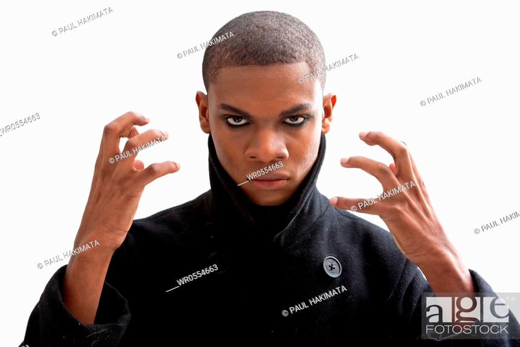 Imagen: African man with smokey eyes, strong expression and black coat, isolated.