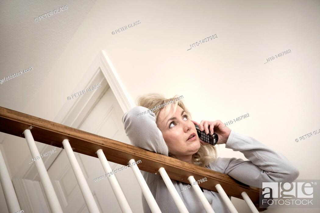 Stock Photo: Middle-age blond woman talking on her telephone.