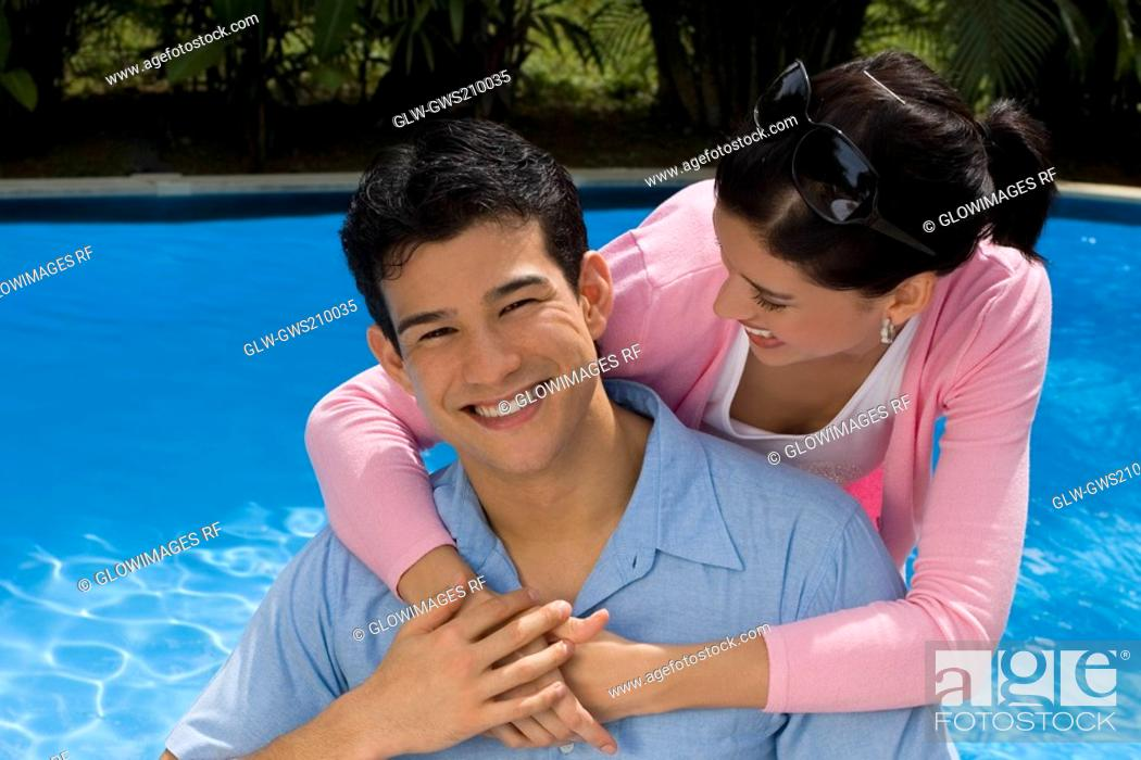 Stock Photo: Young woman embracing a young man from behind and smiling.