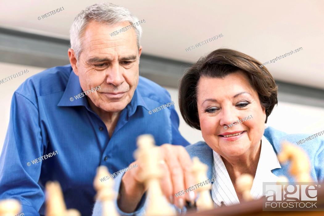 Stock Photo: Germany, Leipzig, Senior man and woman playing chess game, smiling.
