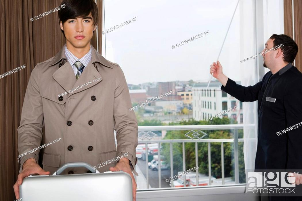 Stock Photo: Portrait of a businessman holding a briefcase with a room service man standing near a window.