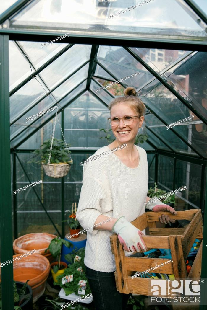 Stock Photo: Portrait of smiling young woman with box of gardening tool in front of greenhouse.