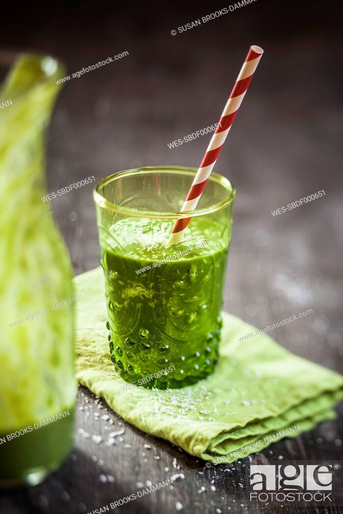 Stock Photo: Glass of spinach smoothie with coconut milk, lemon- and orange juice and banana on napkin and wooden table.