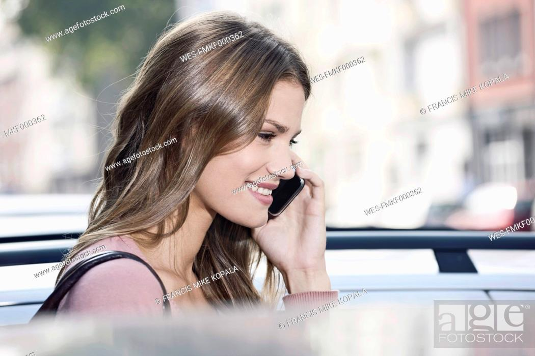 Stock Photo: Germany, Cologne, Young woman on phone, smiling.