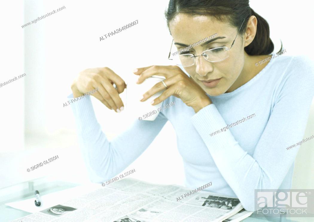 Stock Photo: Woman holding mug looking down at newspaper.