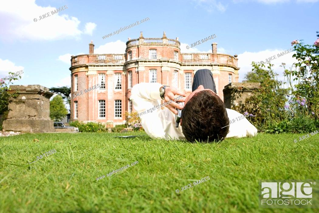 Stock Photo: Young man lying on grass using mobile phone by manor house, ground view.