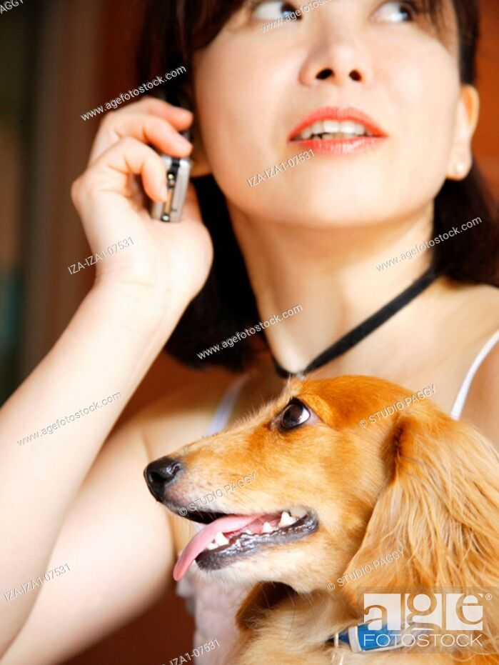 Imagen: Close-up of a mature woman with a dog and talking on a mobile phone.