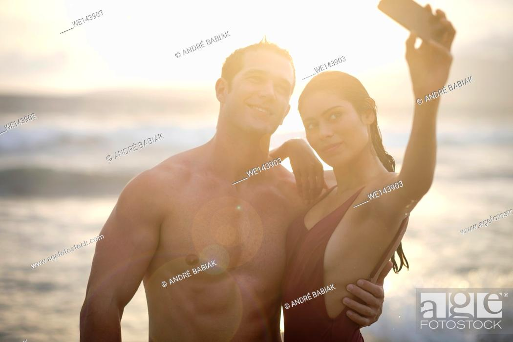 Imagen: Young attractive man and woman are taking a selfie photo at the beach around sunset.