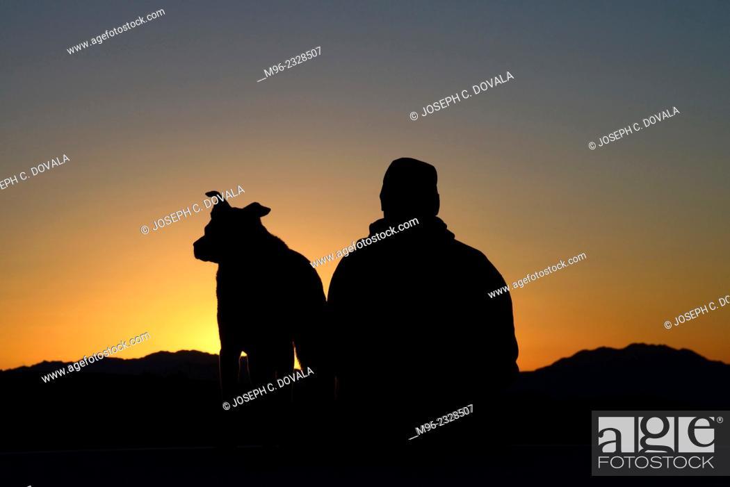 Stock Photo: Dog and master watching sunrise, Mojave Desert, California, USA, MR.