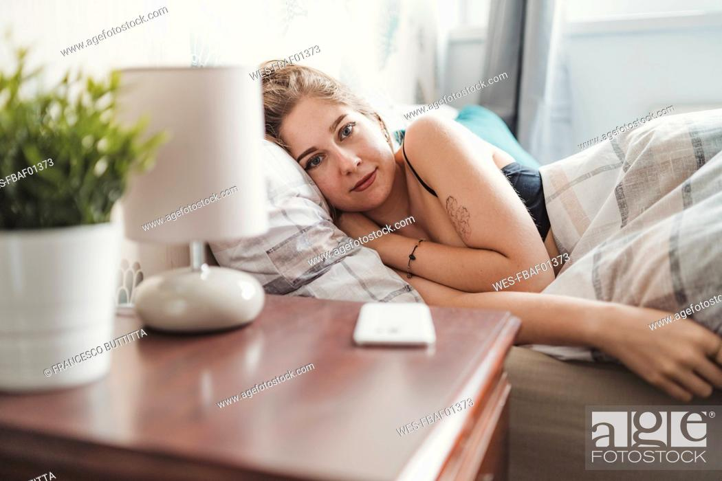 Stock Photo: Portrait of confident attractive young woman lying in bed at home.