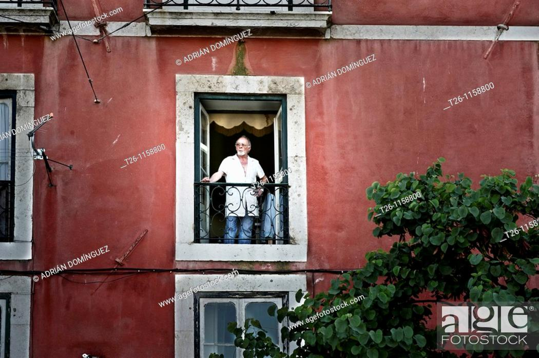Stock Photo: a man looks from his window in the Alfama district. Lisbon, Portugal.