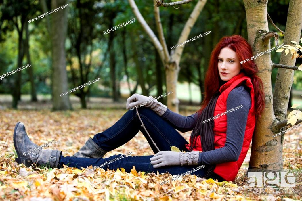Stock Photo: A young woman leaning against a tree.