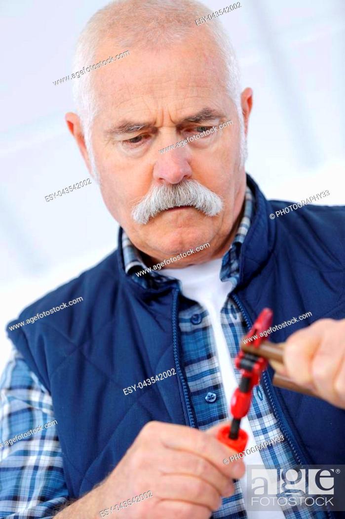 Stock Photo: senior handyman trying to fix something.