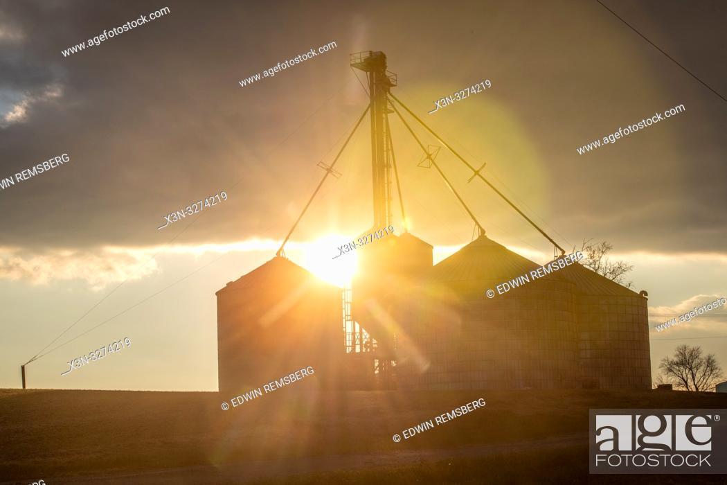 Imagen: The setting sun peaks out behind grain silos, Laytonsville Maryland.