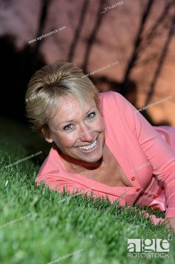 Stock Photo: Middle aged blond woman dressed up playfully on the grass to enjoy the sunset or sunrise.