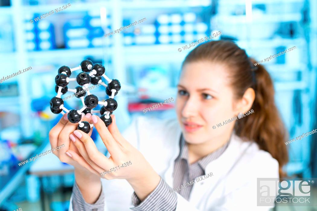 Stock Photo: Female laboratory assistant holding a molecular model.