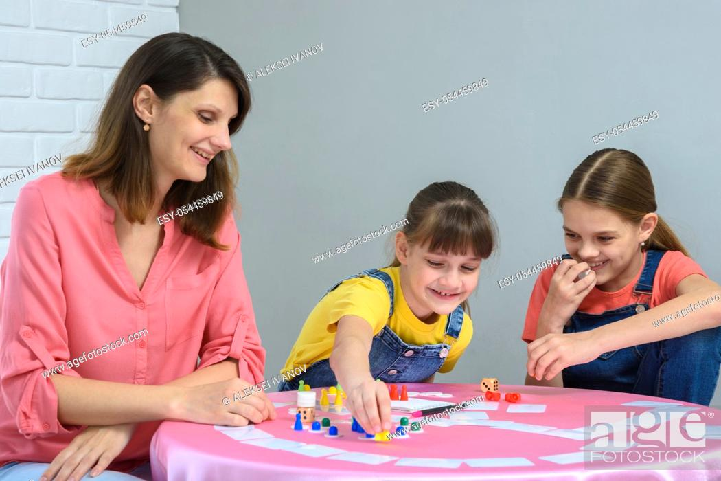 Photo de stock: Girl makes another move playing a board game.