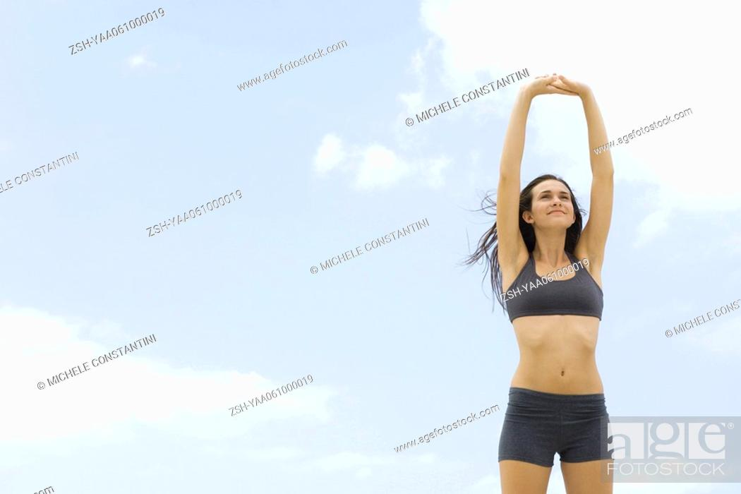 Stock Photo: Young woman in sports bra standing with arms raised, low angle view.