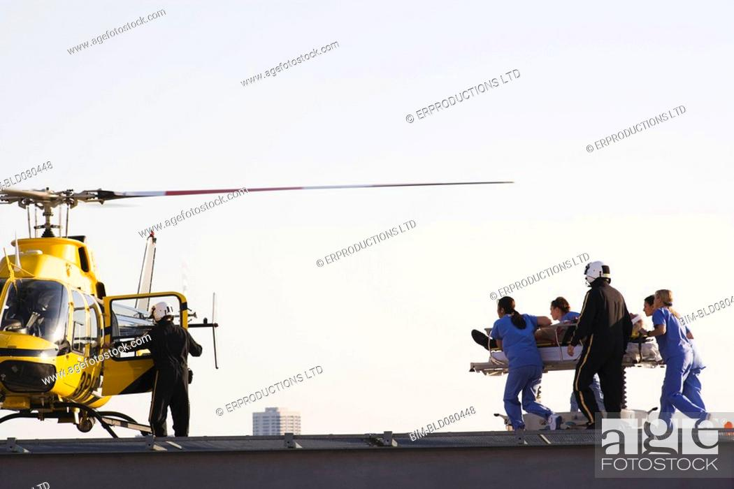 Stock Photo: Medical personnel rushing patient to helicopter.