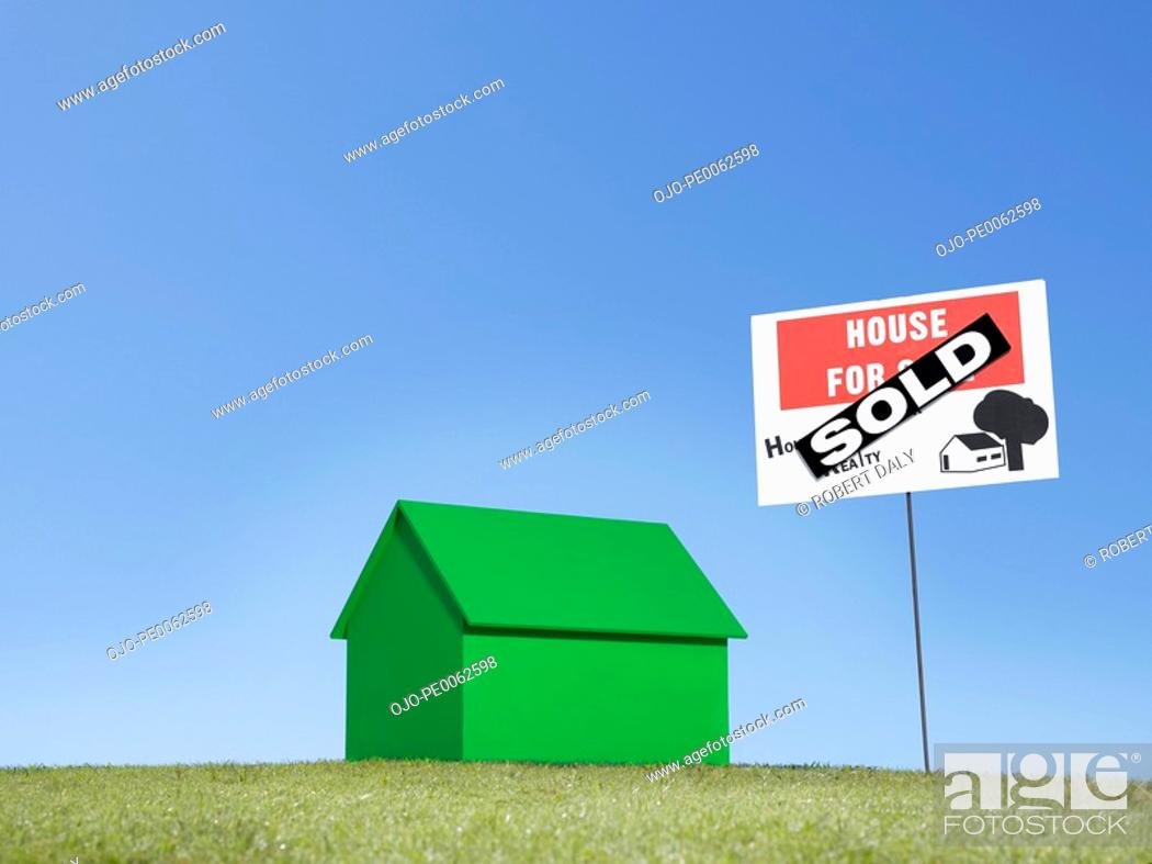 "Stock Photo: Small model house next to ""sold"" sign."