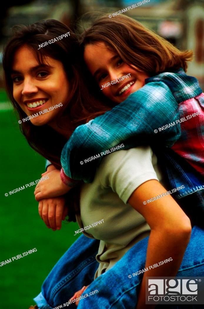 Stock Photo: daughter riding piggyback on mothers back.