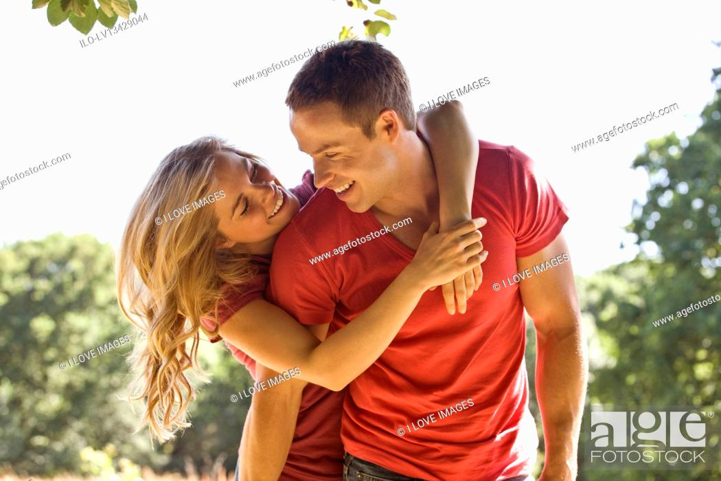 Stock Photo: A young couple embracing, outdoors.