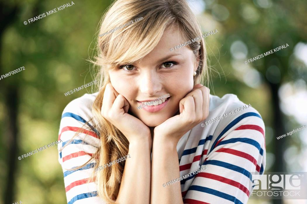 Stock Photo: Germany, Cologne, Young woman smiling, portrait.