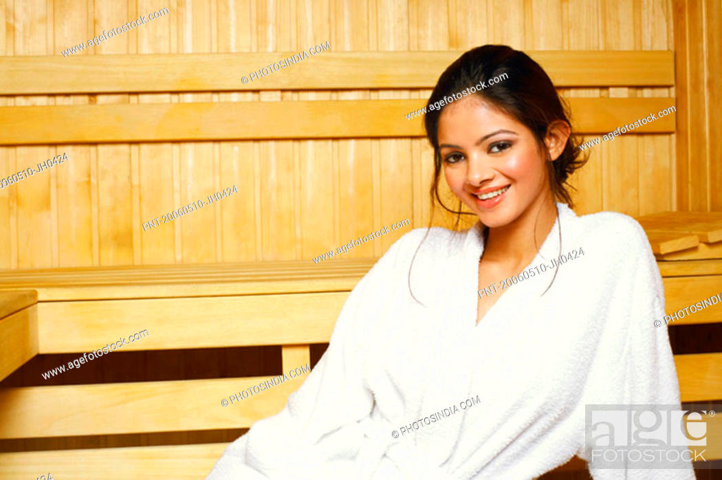 Stock Photo: Portrait of a young woman sitting in a sauna.