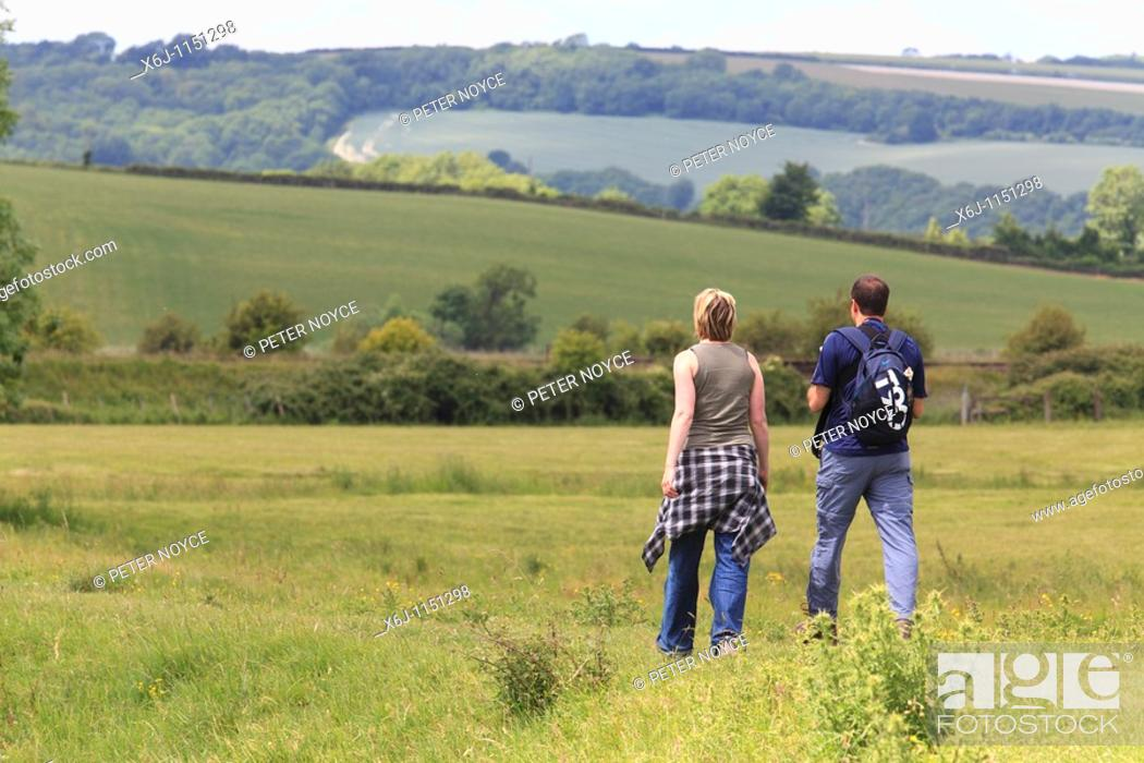 Stock Photo: couple walking away along a path in a field.