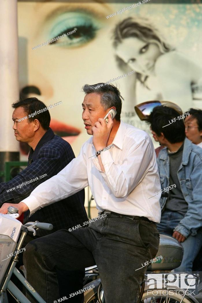 Stock Photo: mobile phone, man on bike with mobile phone.