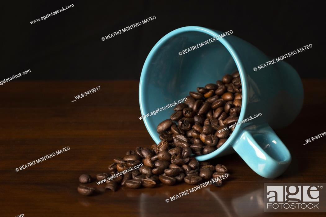 Stock Photo: Blue cup full of coffee beans.