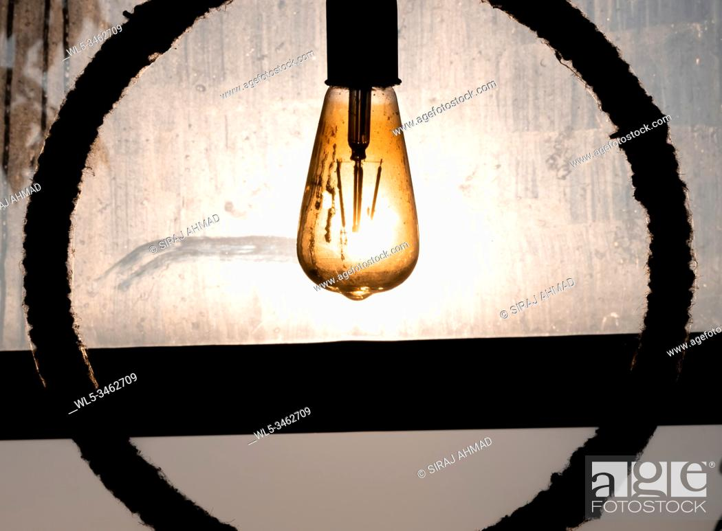 Stock Photo: Silhouetted Light bulb filament againt the rising sun ahnging by the rope.