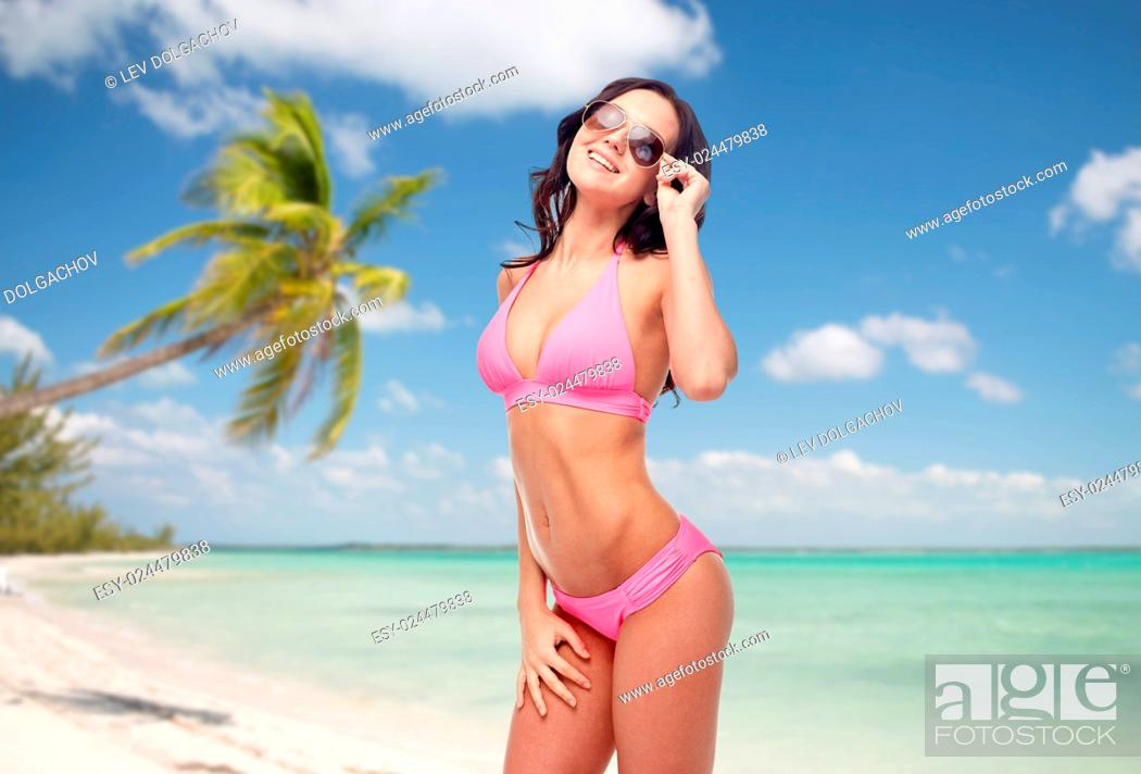 Imagen: people, travel, tourism, swimwear and summer holidays concept - happy young woman in sunglasses and pink swimsuit over exotic tropical beach with palm trees.