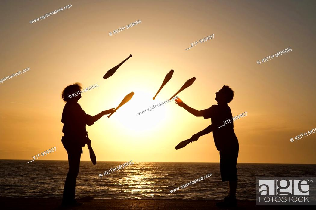 Stock Photo: Two people juggling with clubs at sunset on Aberystwyth promenade wales UK.