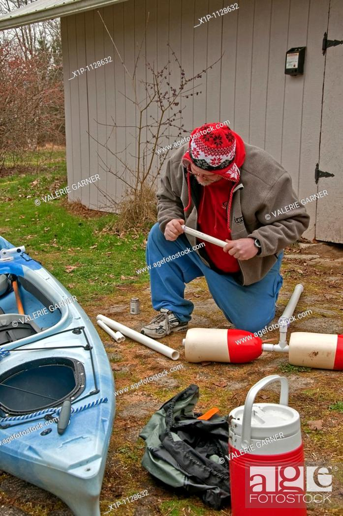 Stock Photo: This middle aged man is preparing for kayak season in early spring by building an outrigger for his kayak out of PVC pipe.