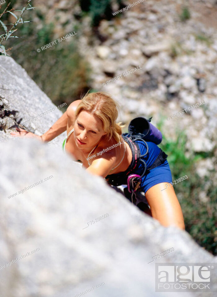 Stock Photo: Young woman rock climbing in California.