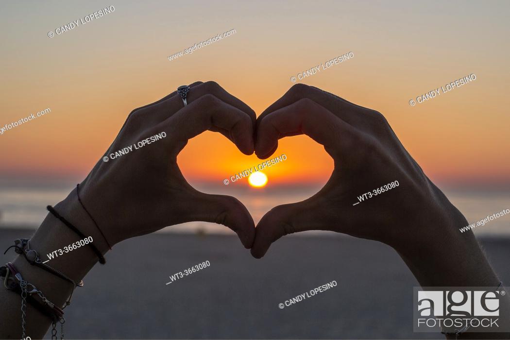 Photo de stock: Girlâ. . s hands making a heart that surrounds the Sun at sunset.